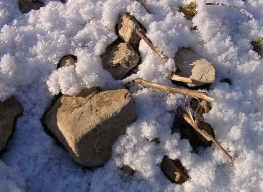 Schnee auf steinigem Acker